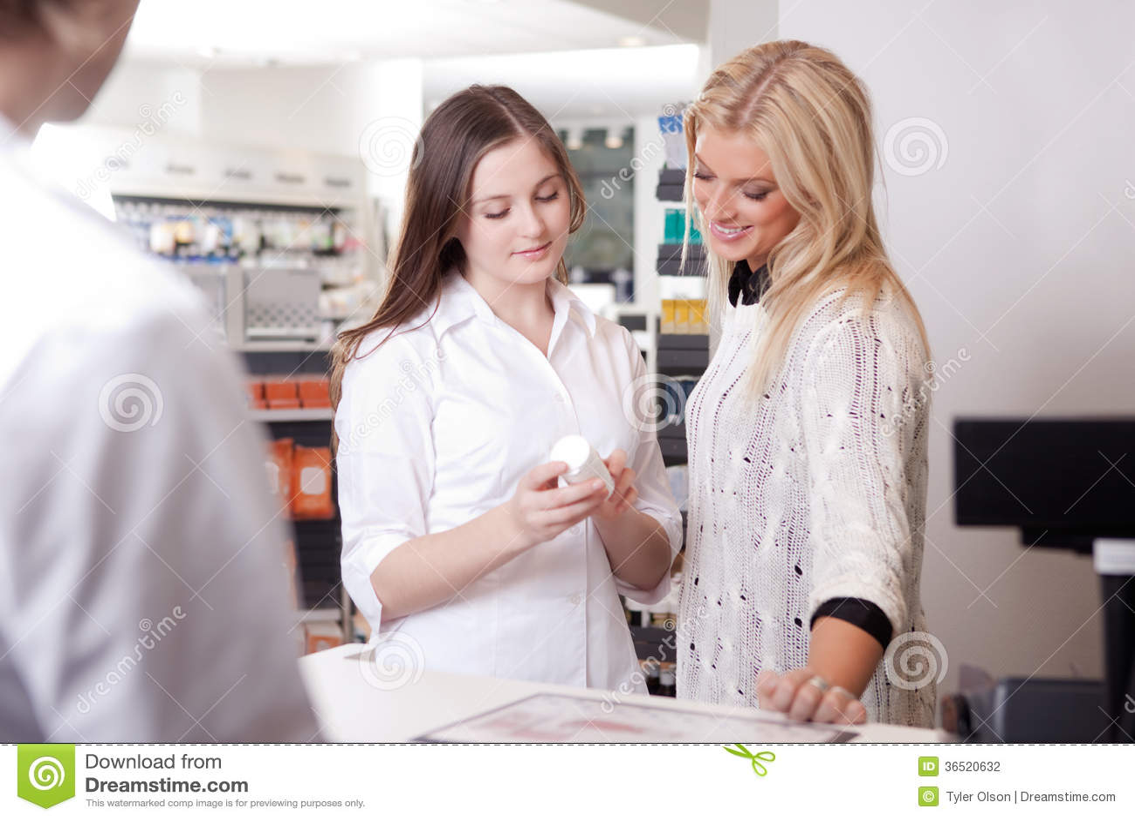 Female Pharmacist Advising Customer At Pharmacy Stock Photo Image