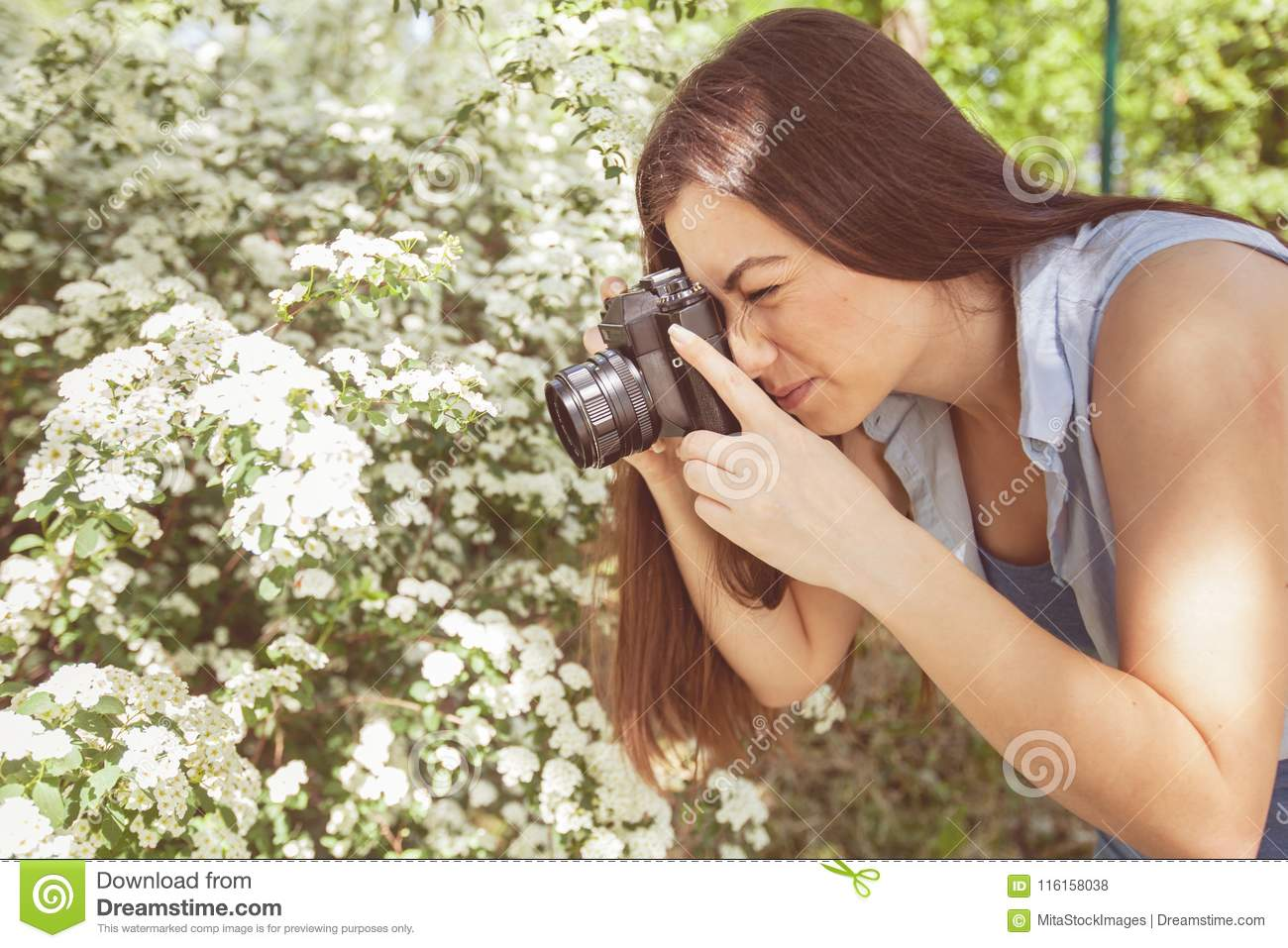 Female amateur photographer taking photo of flower with retro old camera in  summer park at beautiful sunny day
