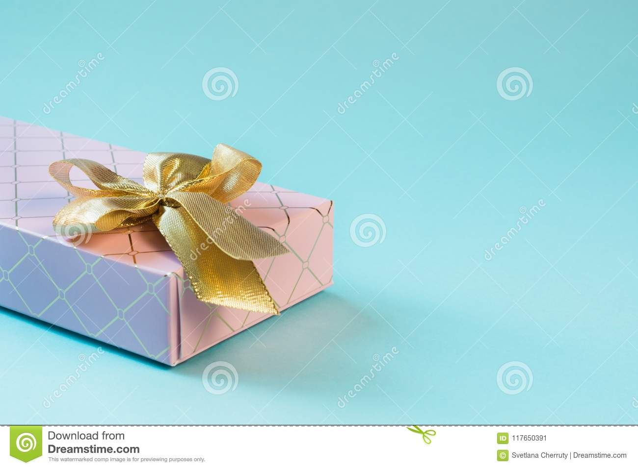 Female pink gift box with golden ribbon on punchy pastel blue. Birthday. Copy space.