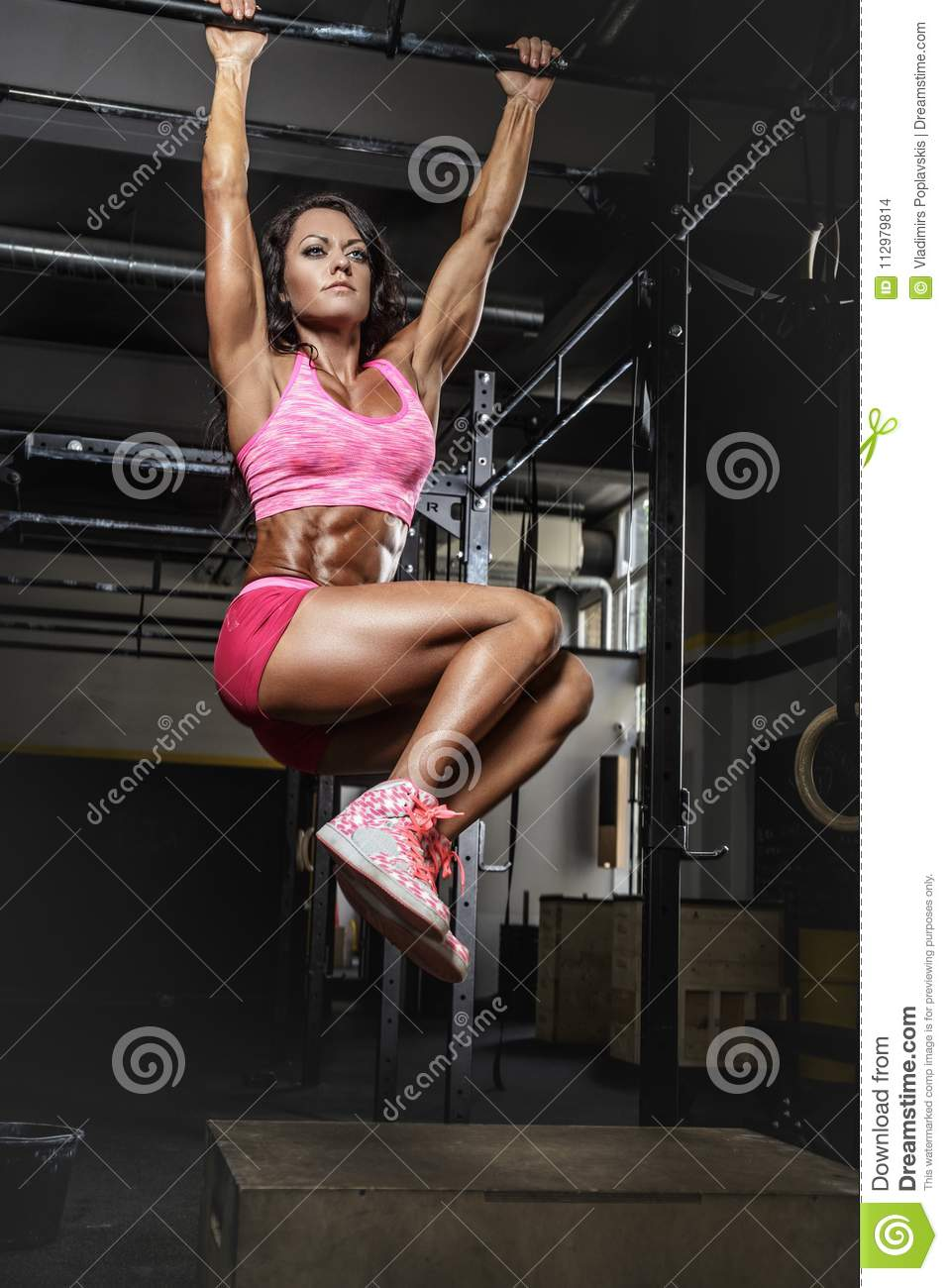 Female in pink sportswear doing exercises on horizontal bar.