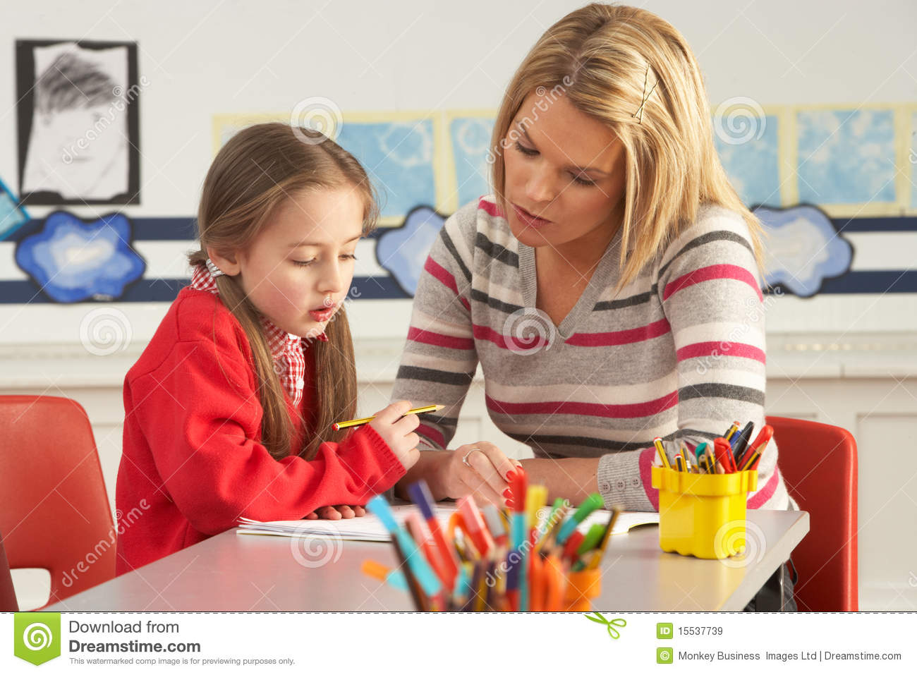 Female Primary School Pupil And Teacher Working