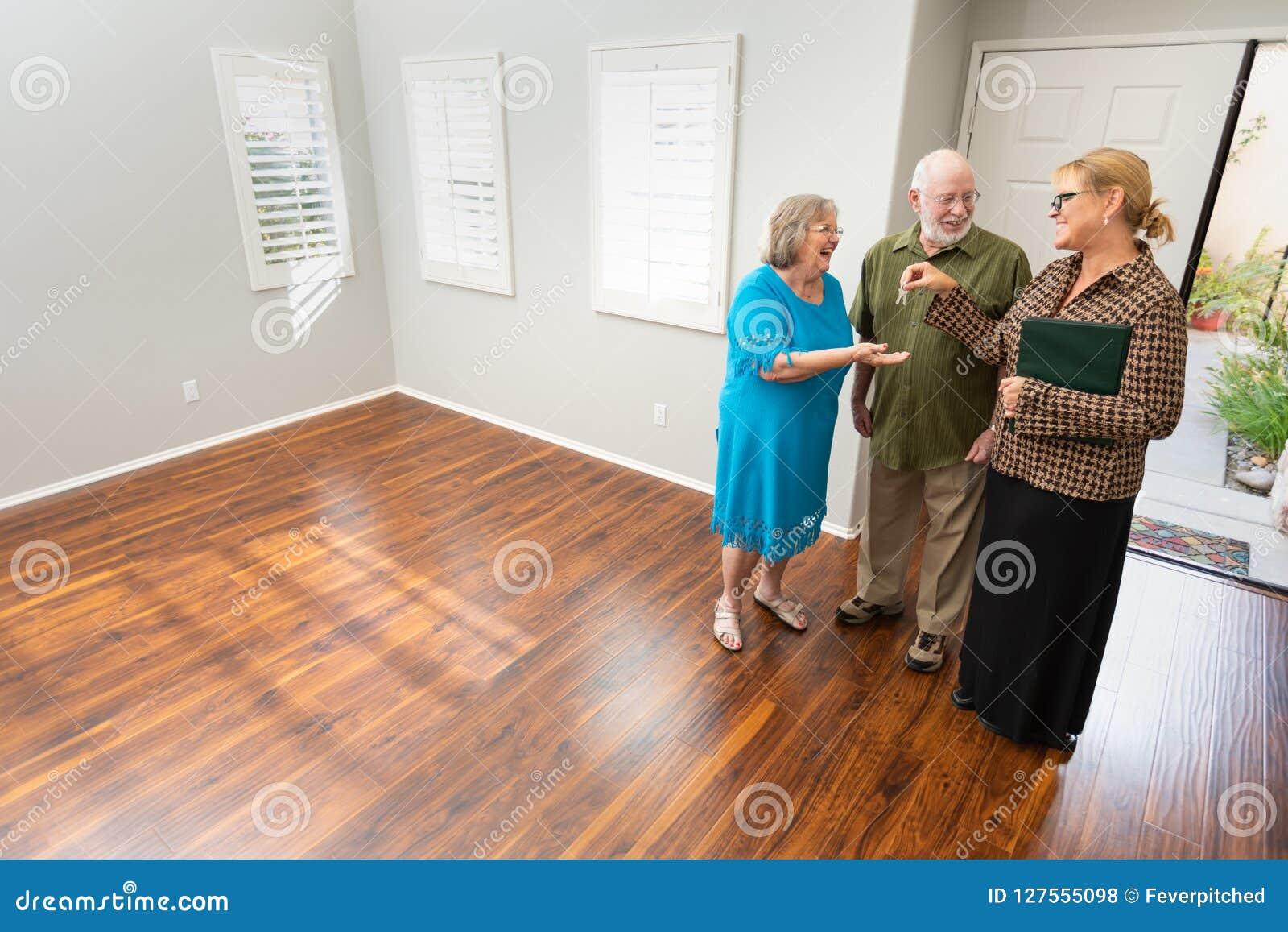 Female Real Estate Agent Handing New House Keys to Senior Adult