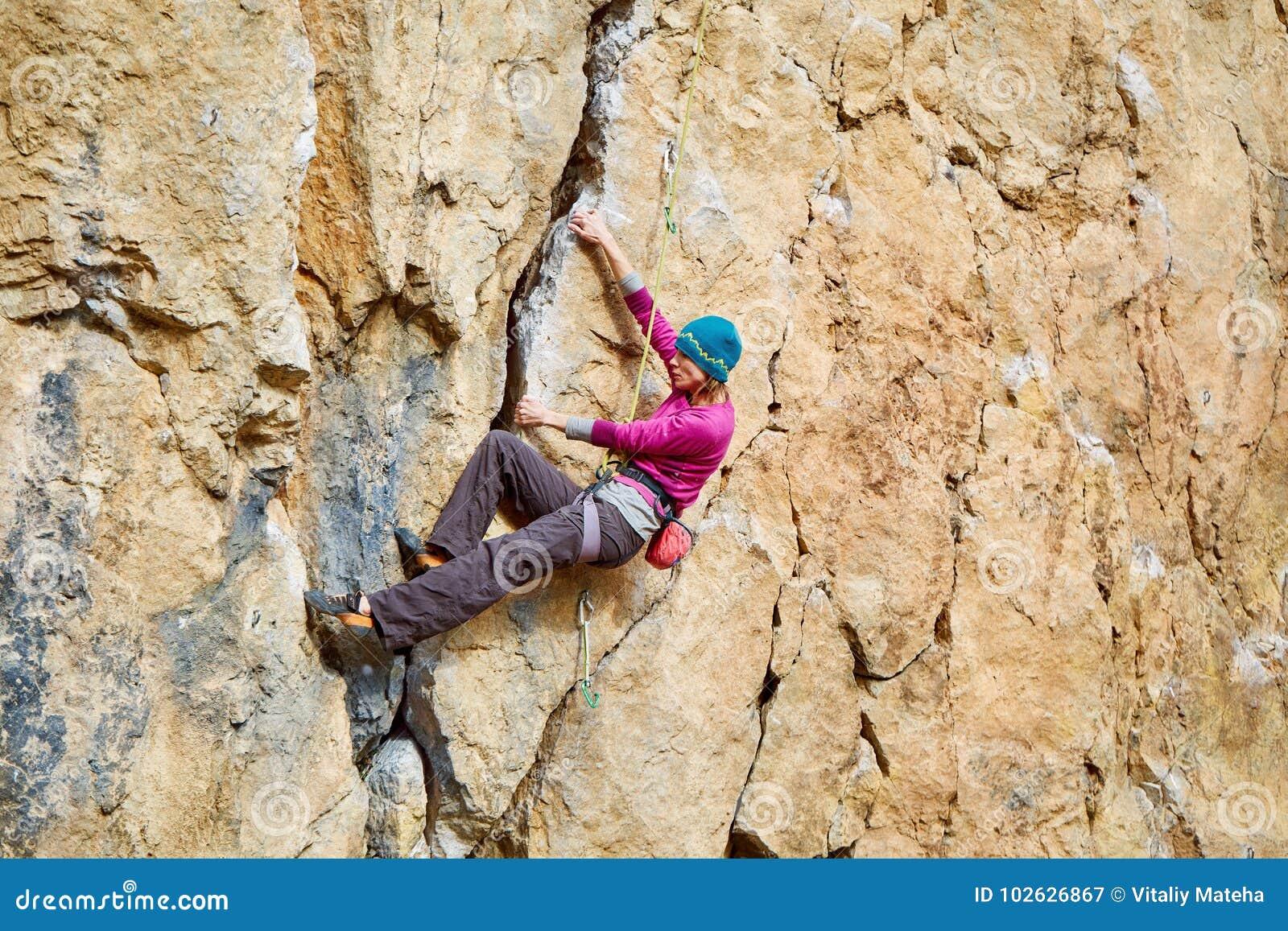 Female rock climber on overhanging cliff, Kalymnos Island