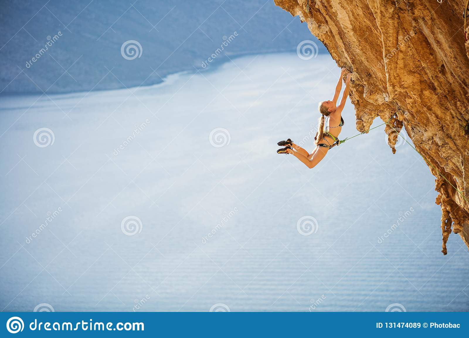 Female rock climber jumping on handholds on challenging route on cliff