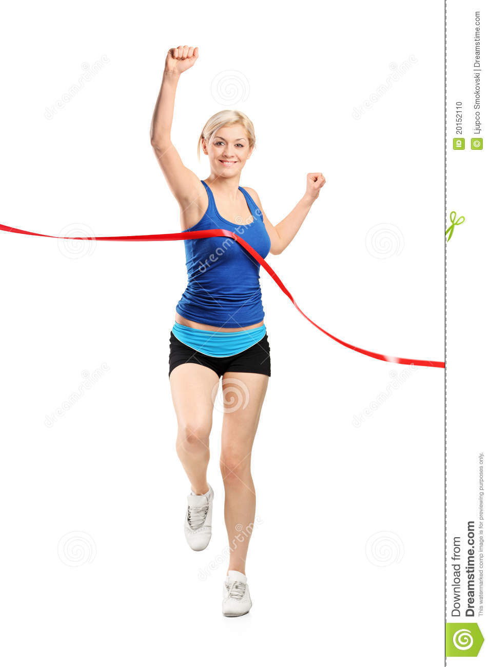 female runner running towards a finish line stock photo