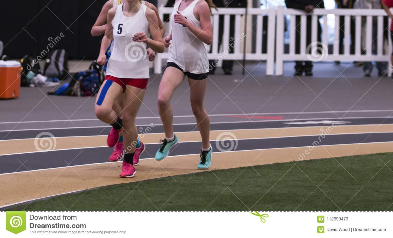 Female runners on indoor track with kinesio tape on leg