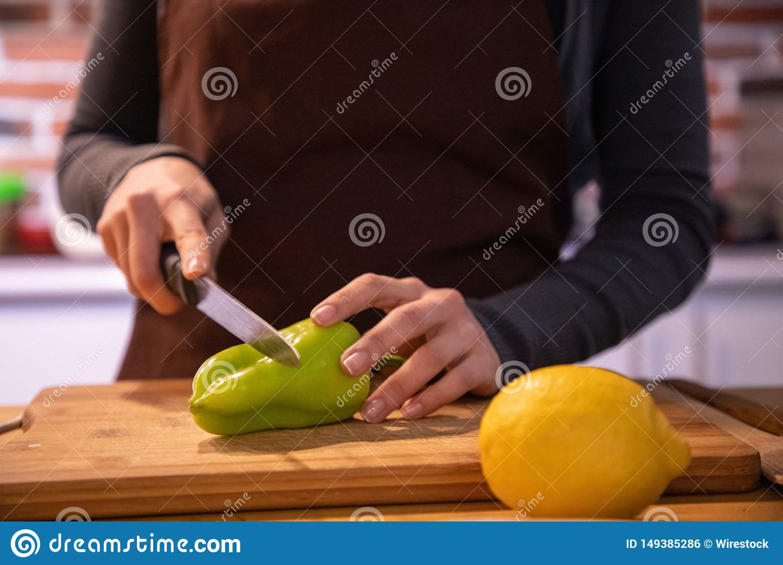 Female`s hand cutting vegetables in the kitchen
