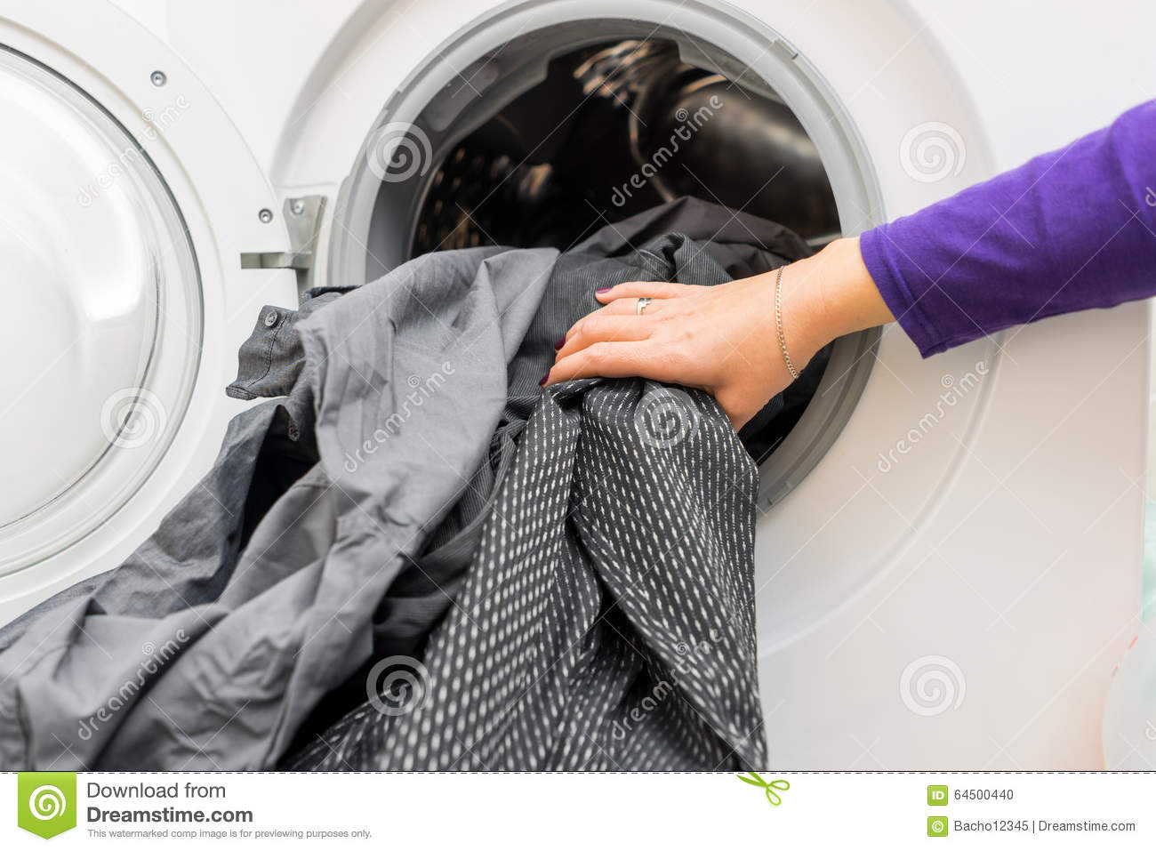 Female s hands putting dirty clothes into washing machine