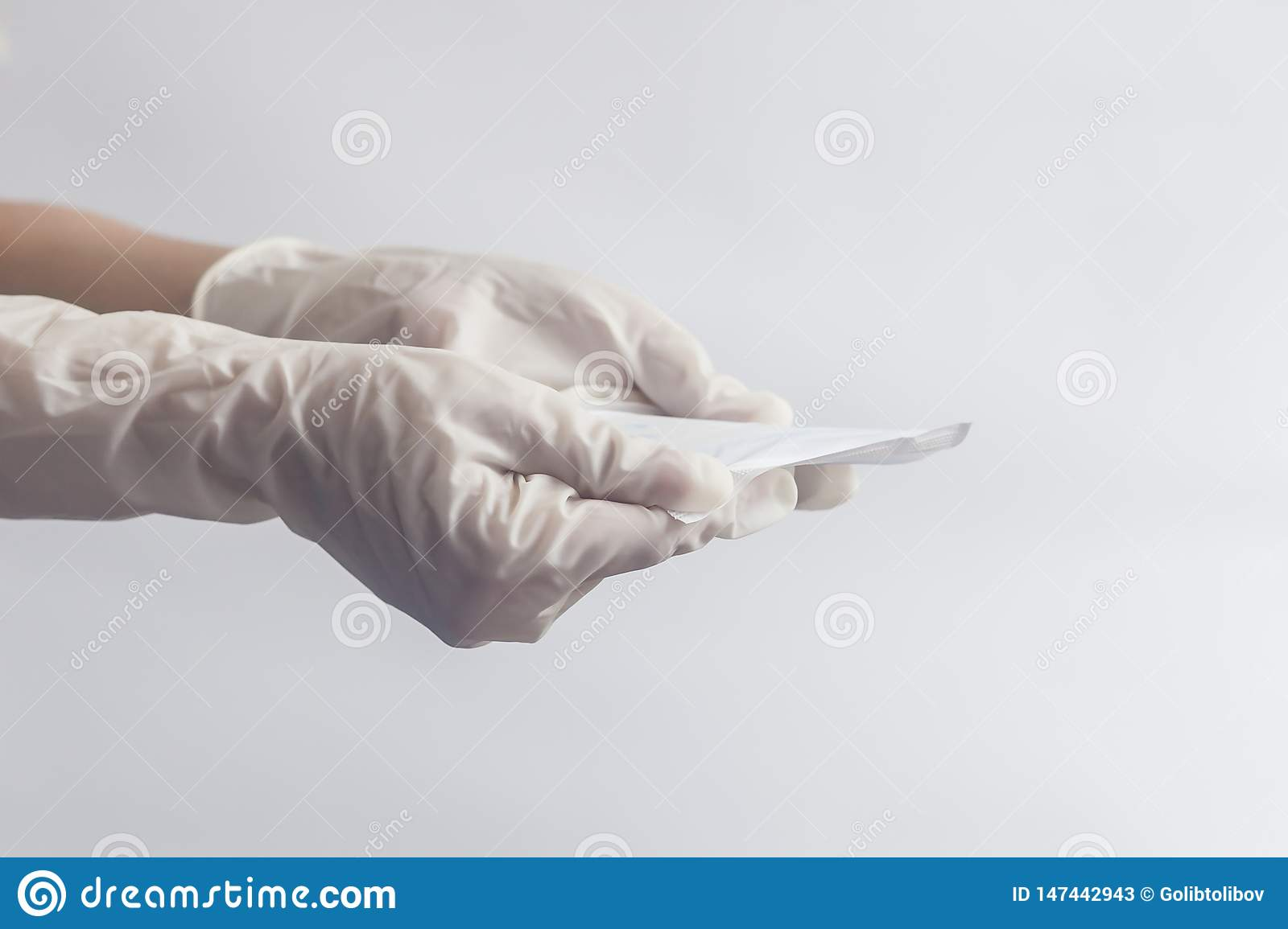 Female`s hygiene products. Woman`s hands in medical gloves holding sanitary napkins against white background. Period days concep