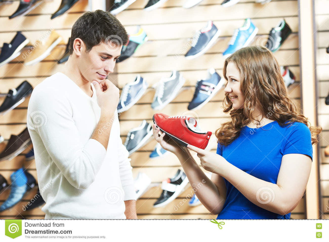 50b8e28f8b Female Sale Assistant Demonstrates Shoe To Man At Footwear Shop ...