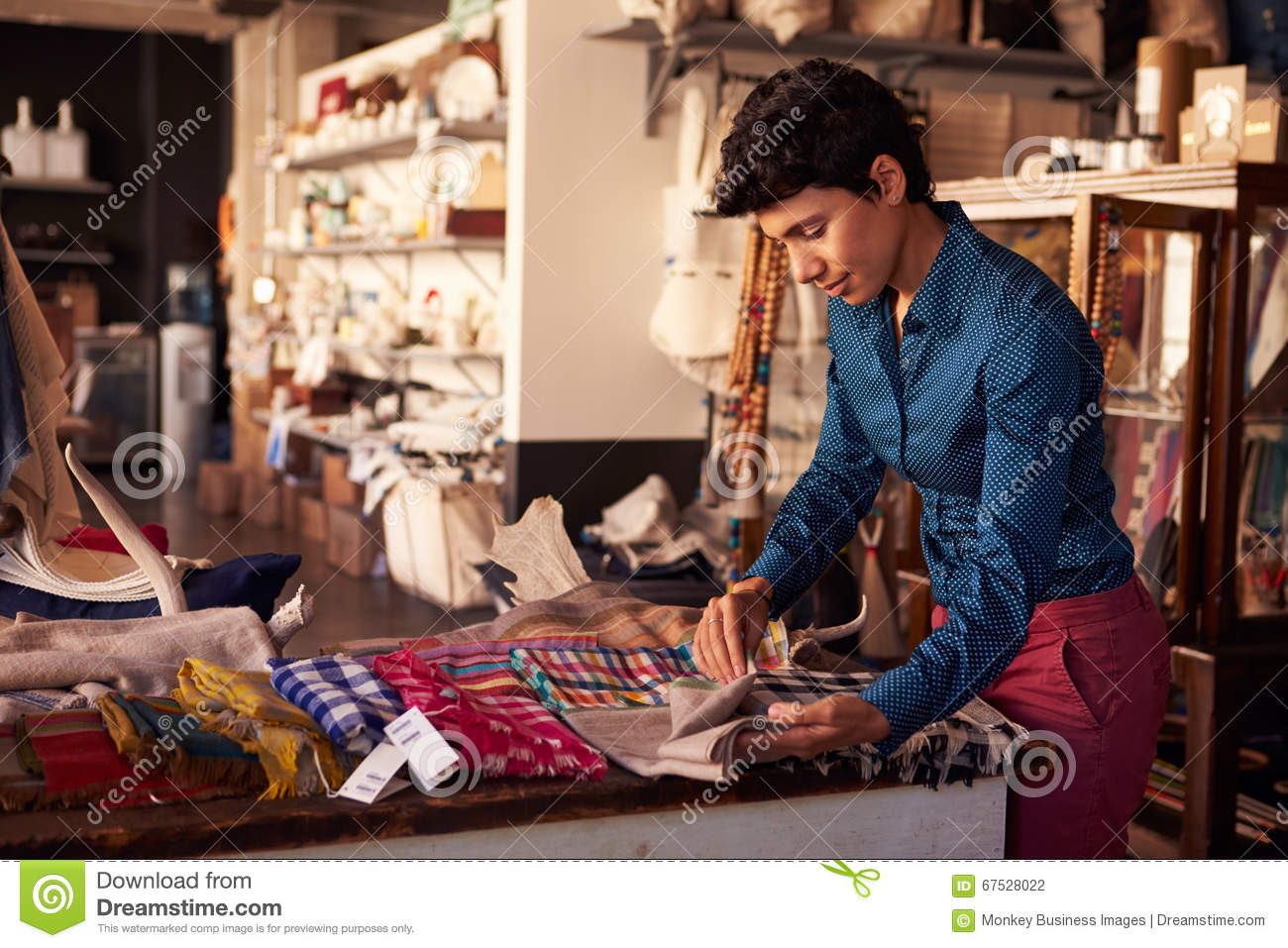 Female Sales Assistant Arranging Textiles In Homeware Store