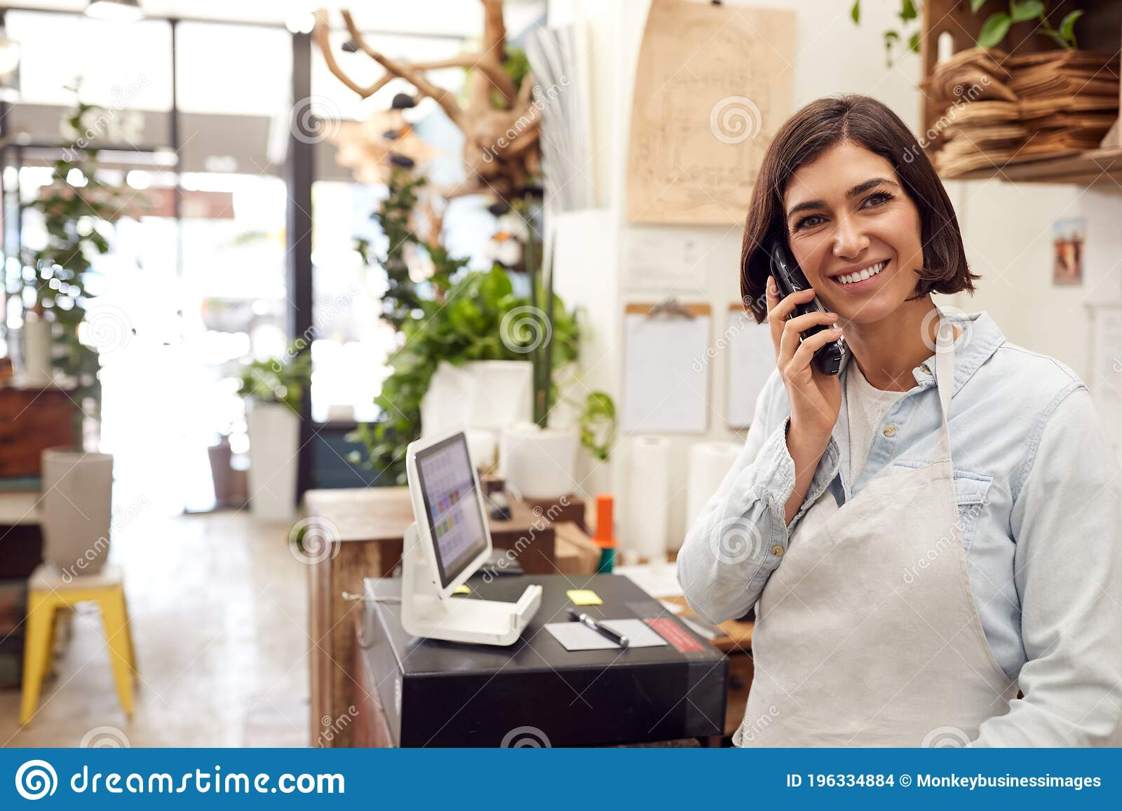 Female Sales Assistant Taking Phone Call Behind Sales Desk ...