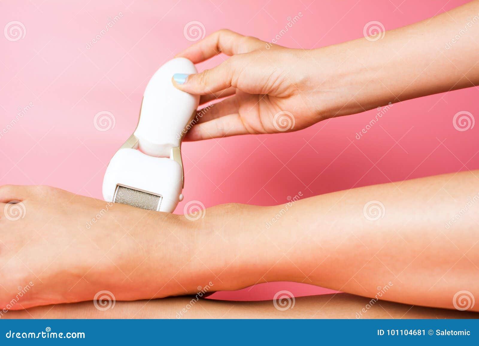 Female scrubbing hard skin from feet