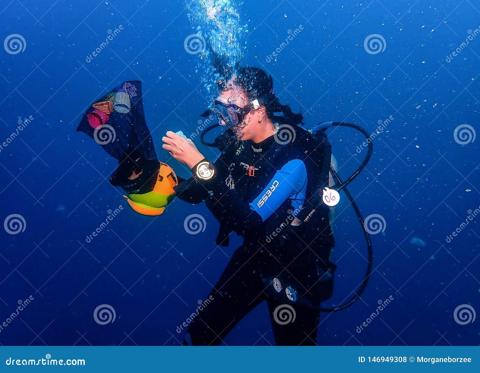 Female scuba diver underwater performing a dexterity exercise