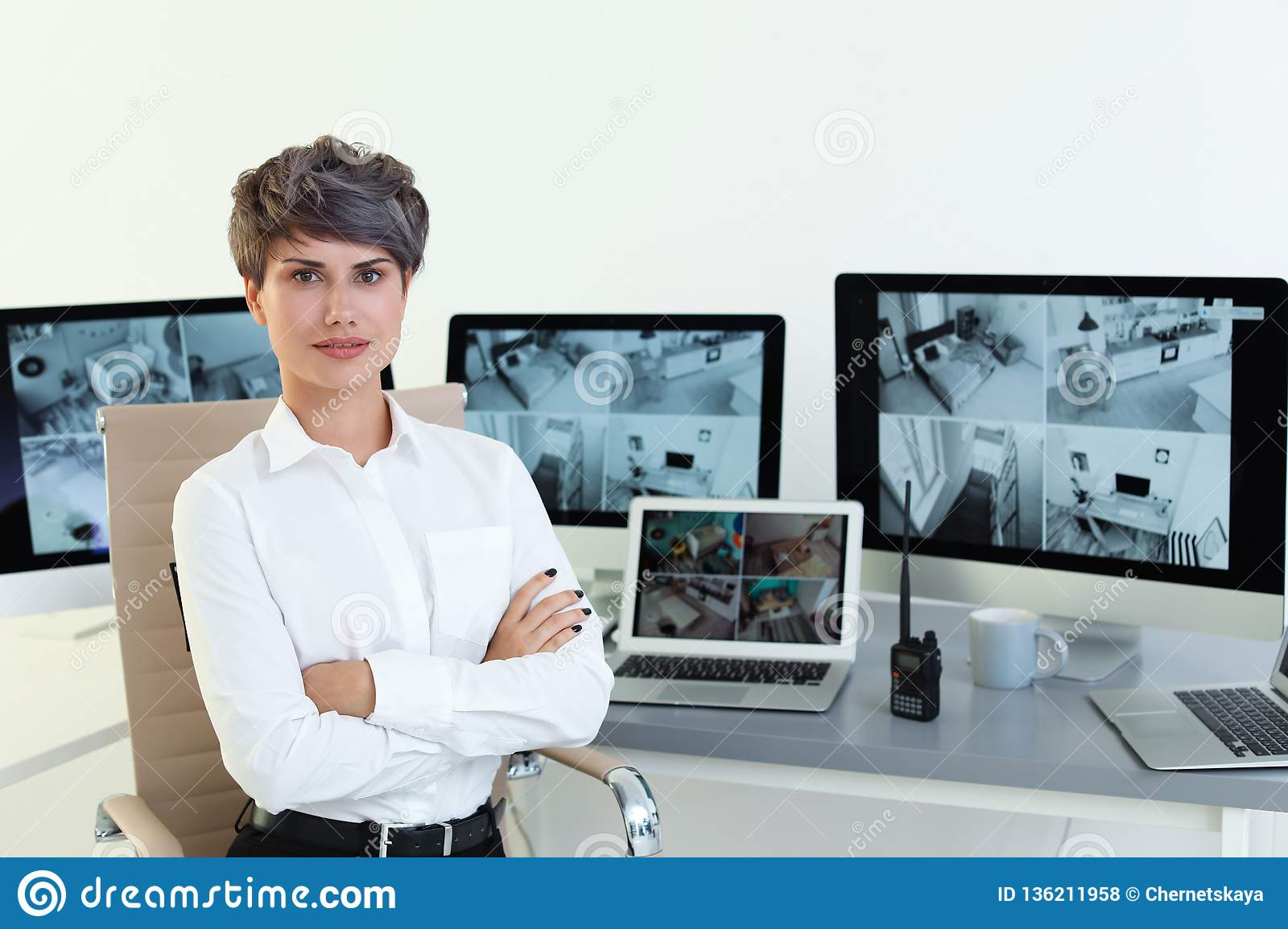 Female security guard at workplace with modern computers