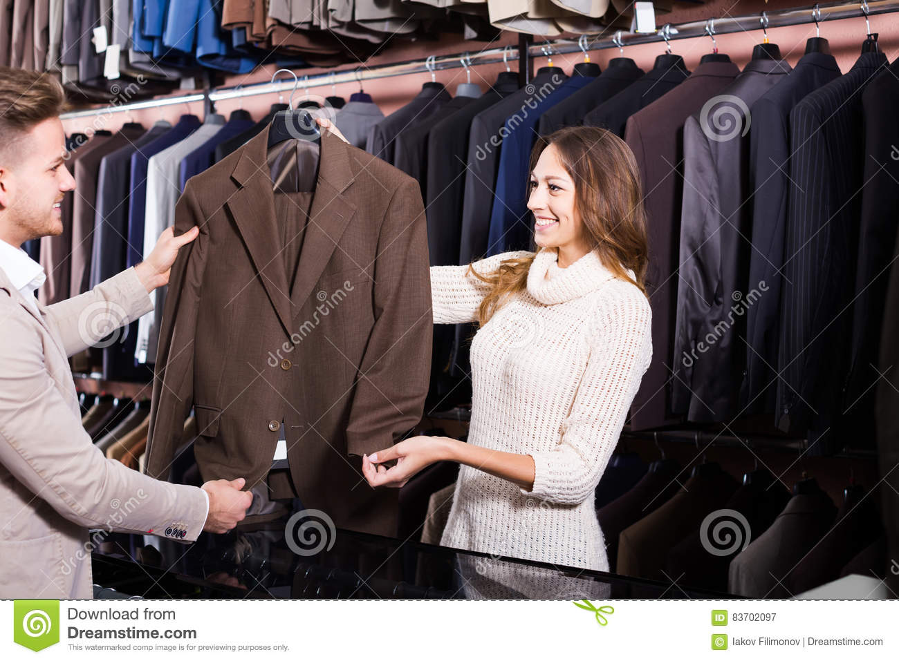 Female Shopping Assistant Offering Various Suits In Men's Clot Stock Photo