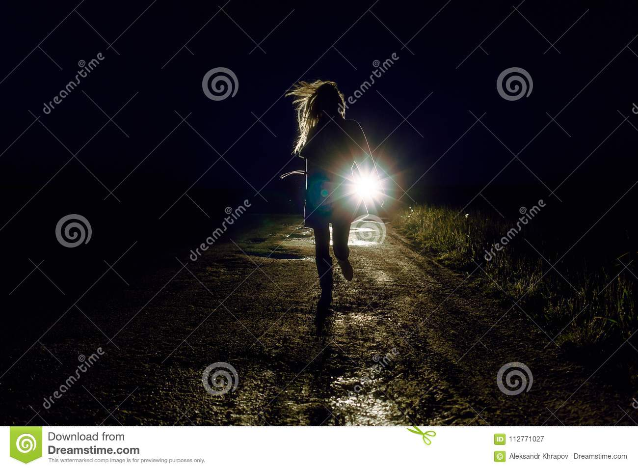 female silhouette on a night country road running away from pursuers by car in the light of headlights