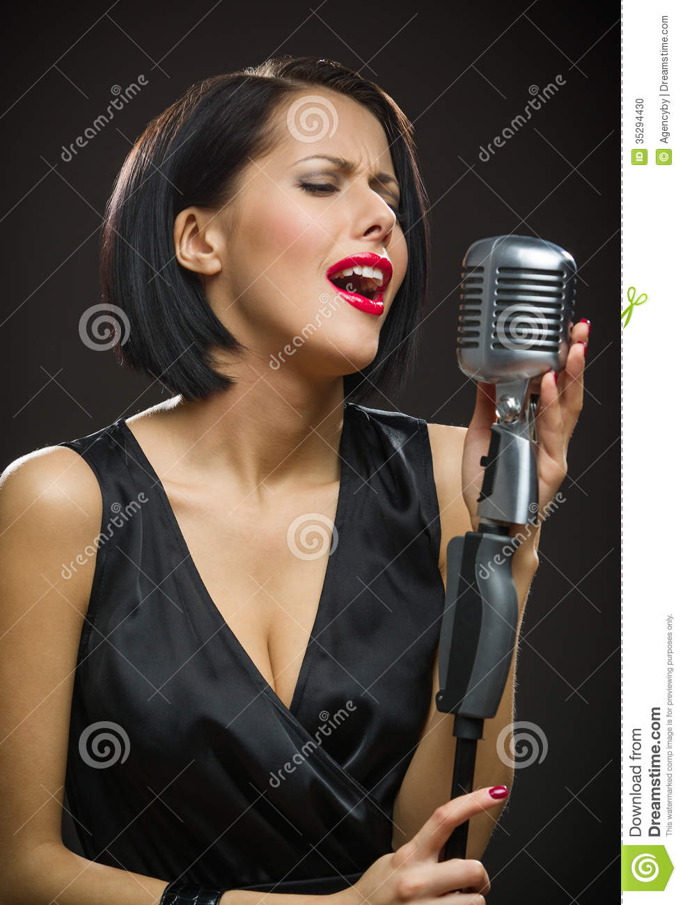 Female singer with closed eyes keeping microphone