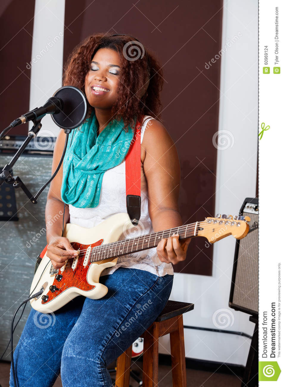 Female Singer With Eyes Closed Playing Guitar In Stock