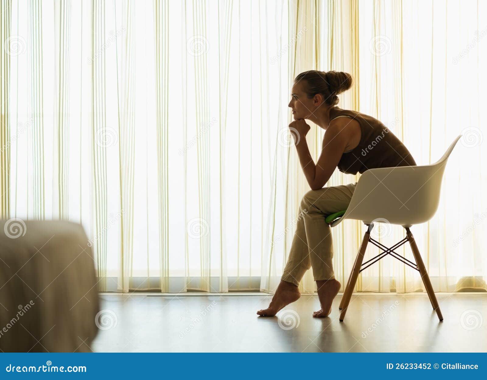 Female Sitting Near Window In Thoughtful Pose Stock