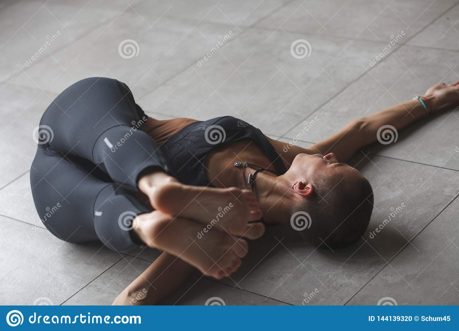 Female in sportswear doing twist and stretch exercise