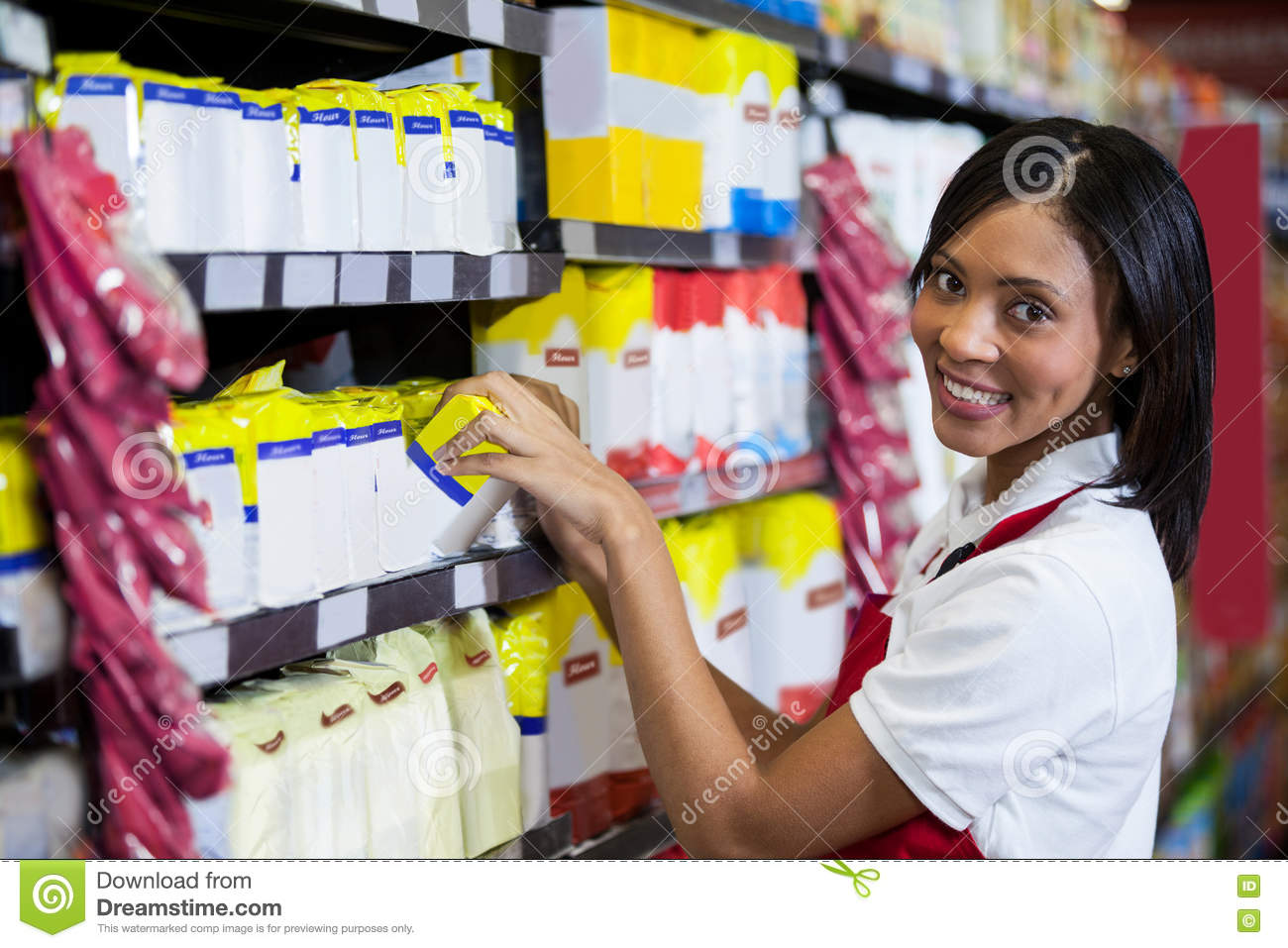 Female staff arranging goods in grocery section