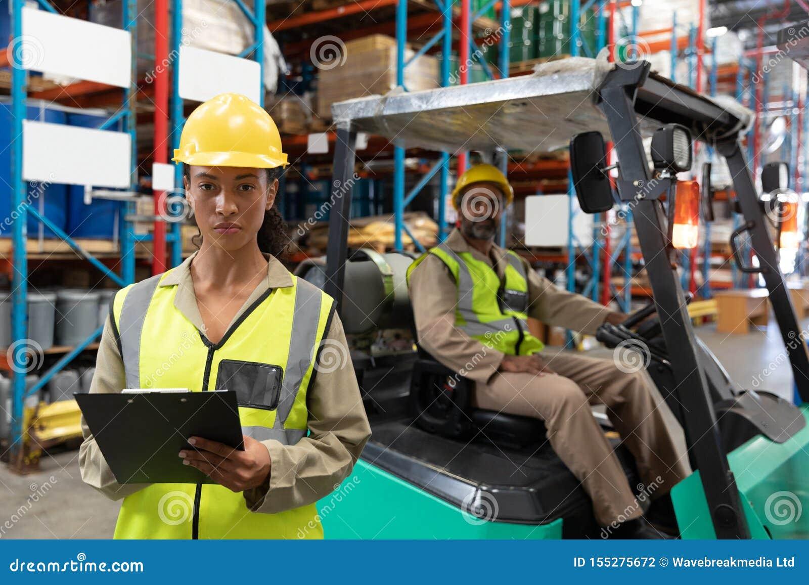 Female staff writing on clipboard in warehouse