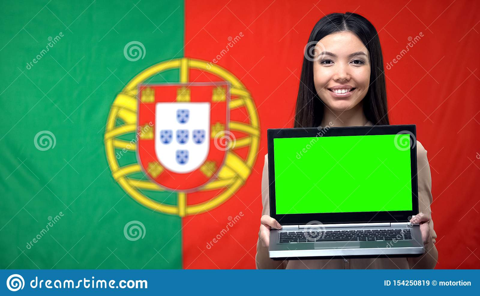 Female student holding laptop with green screen, Portuguese flag on background