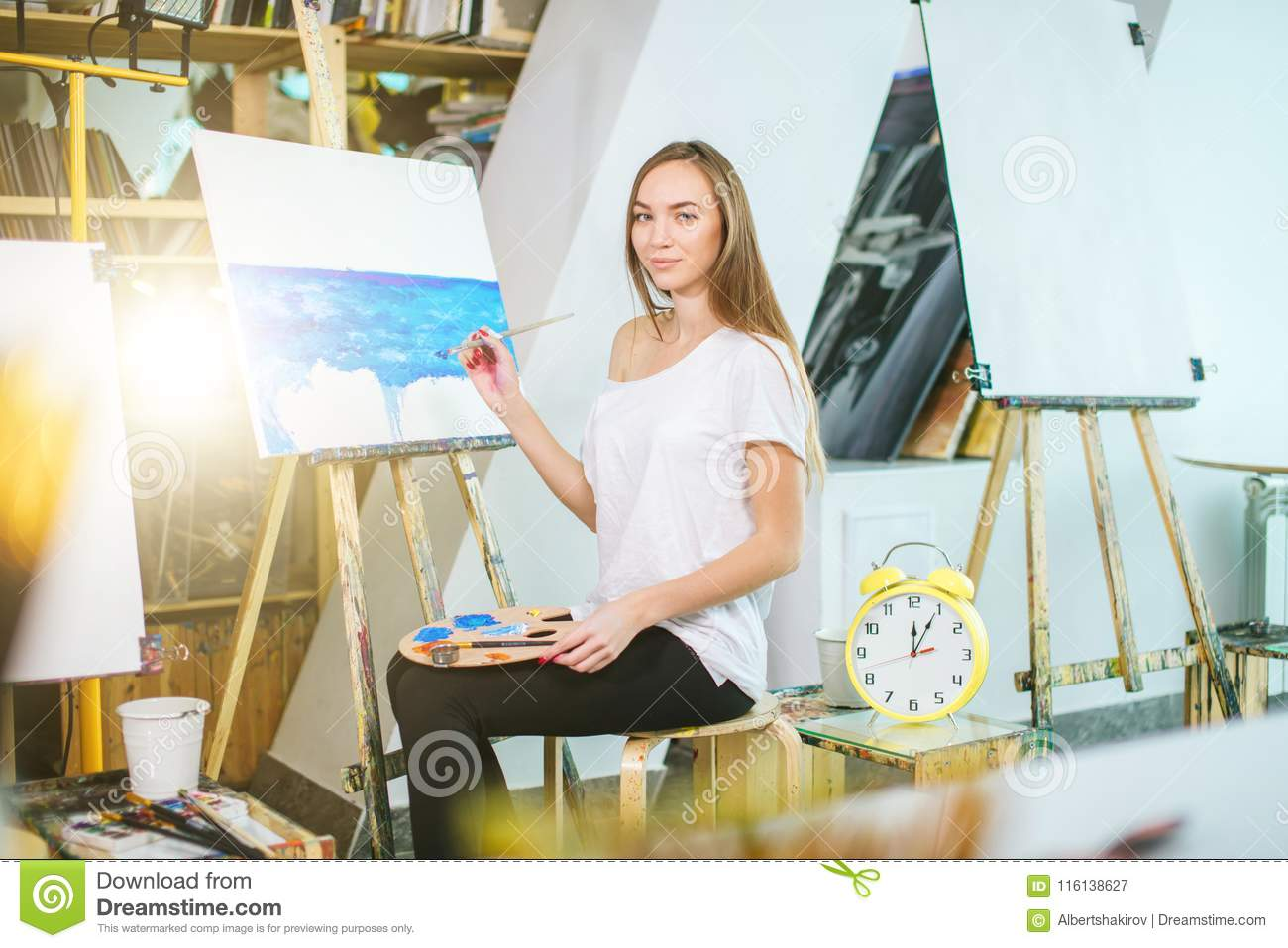 Woman Artist Painting A Picture On Easel With Oil Paints In