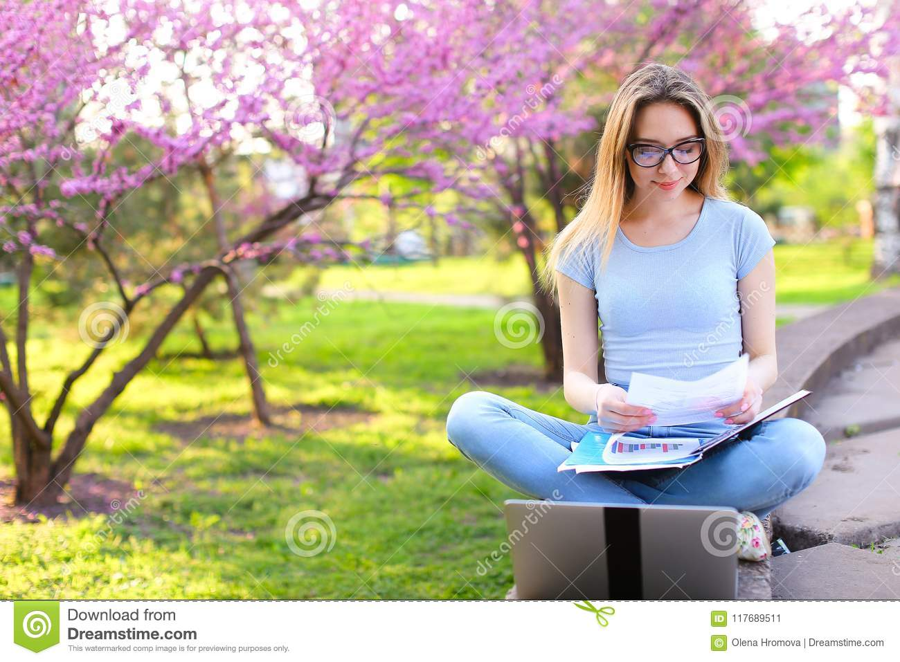 Female student studying with laptop and papers in blooming park.