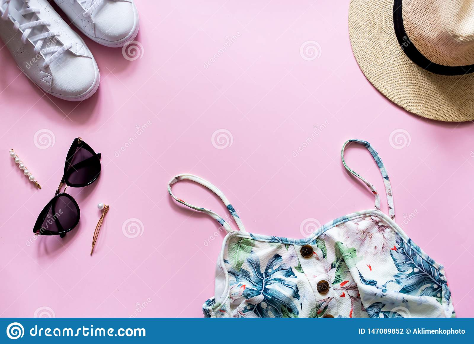 Female summer outfit on pink backgroud. Printed summer dress with straw hat, sunglasses and white sneakers.