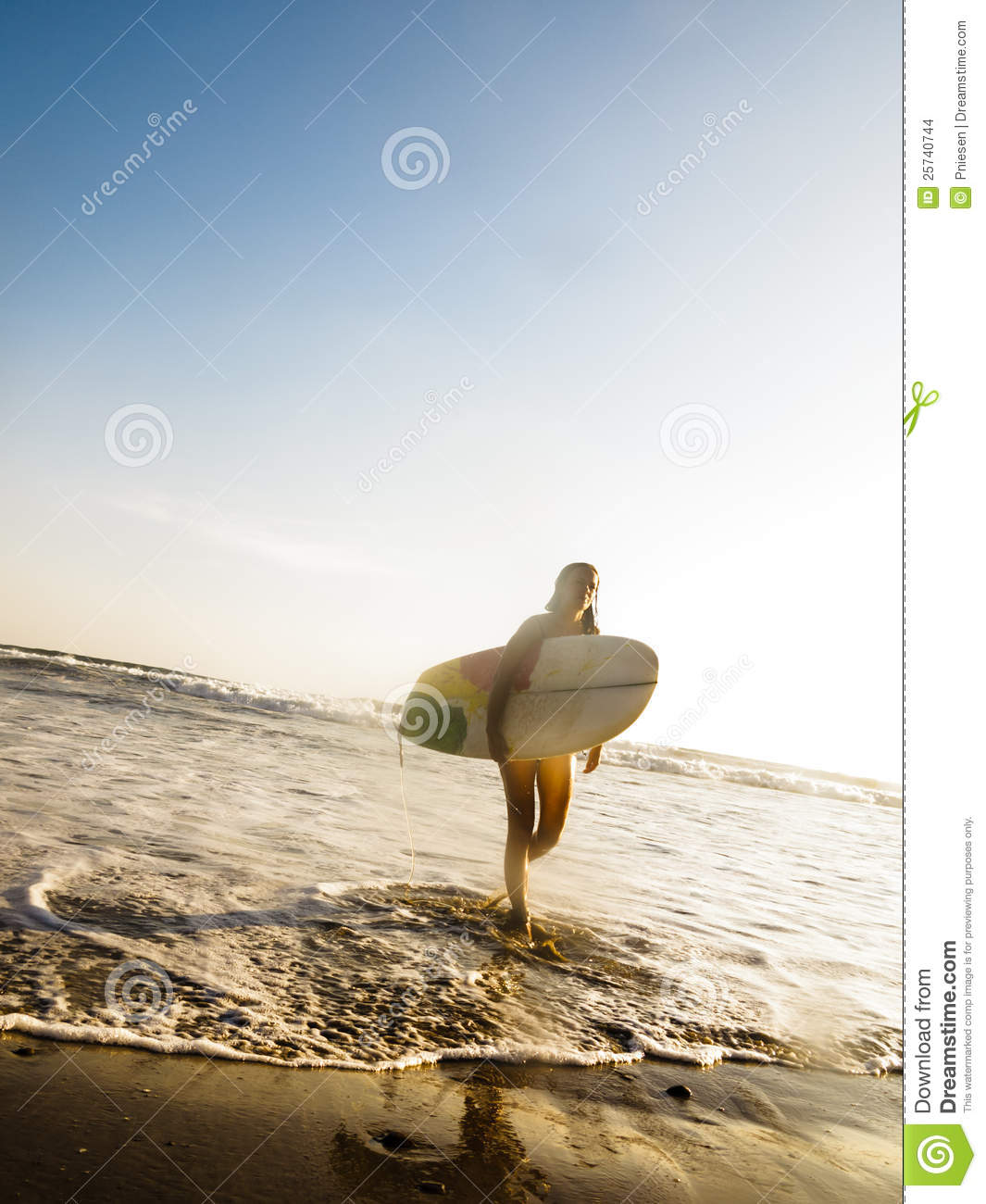 Female surfer with surf board walking on beach
