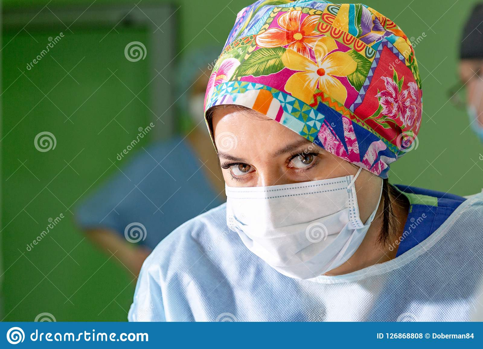 Female surgeon doctor wearing protective mask and hat during the operation. Healthcare, medical education, emergency