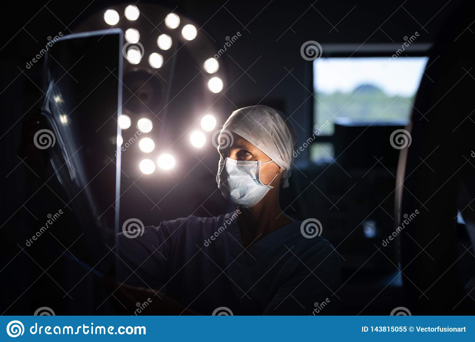 Female surgeon looking at x-ray picture in operation room