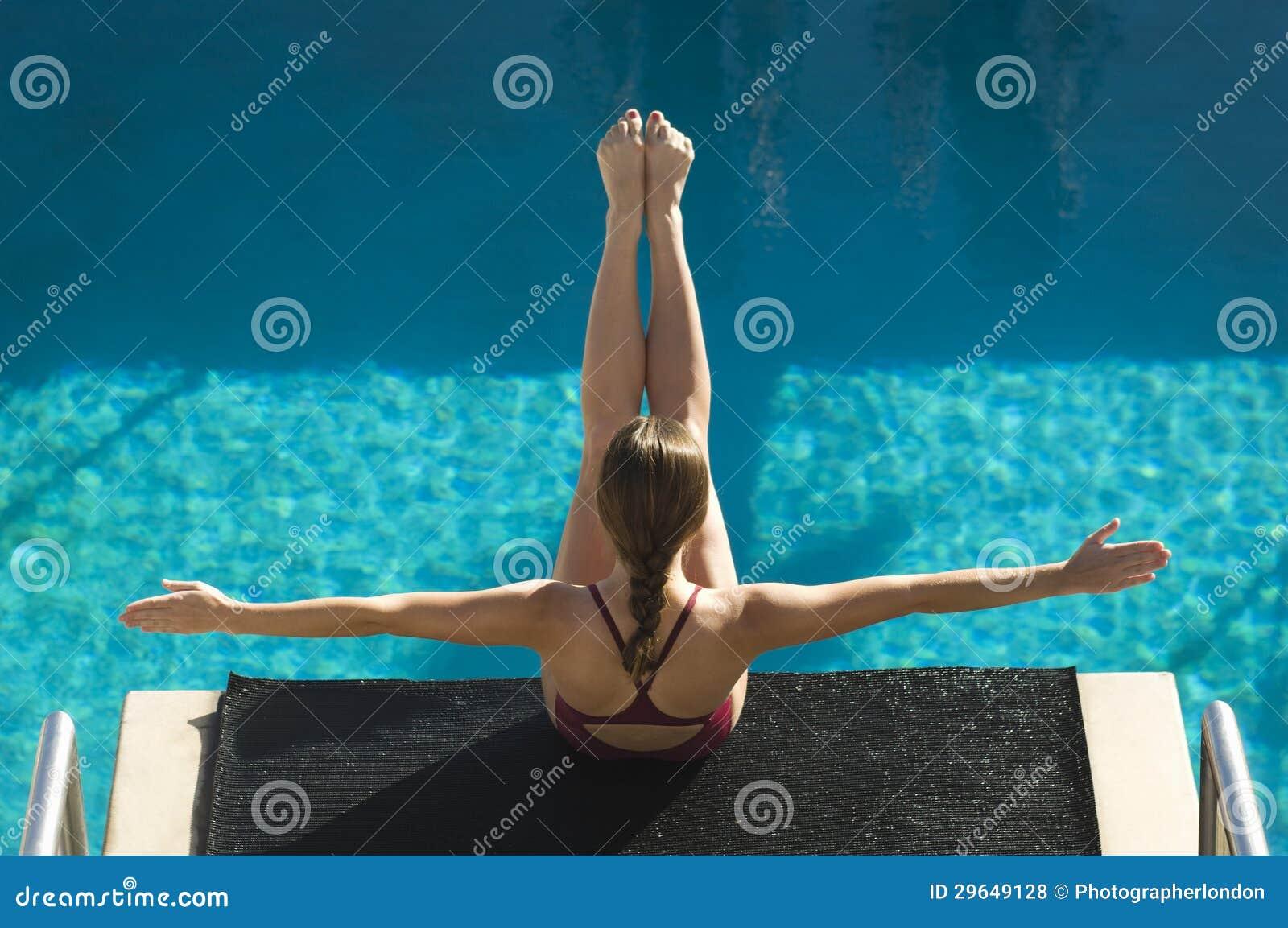 Female Swimmer Sitting On Dive Board