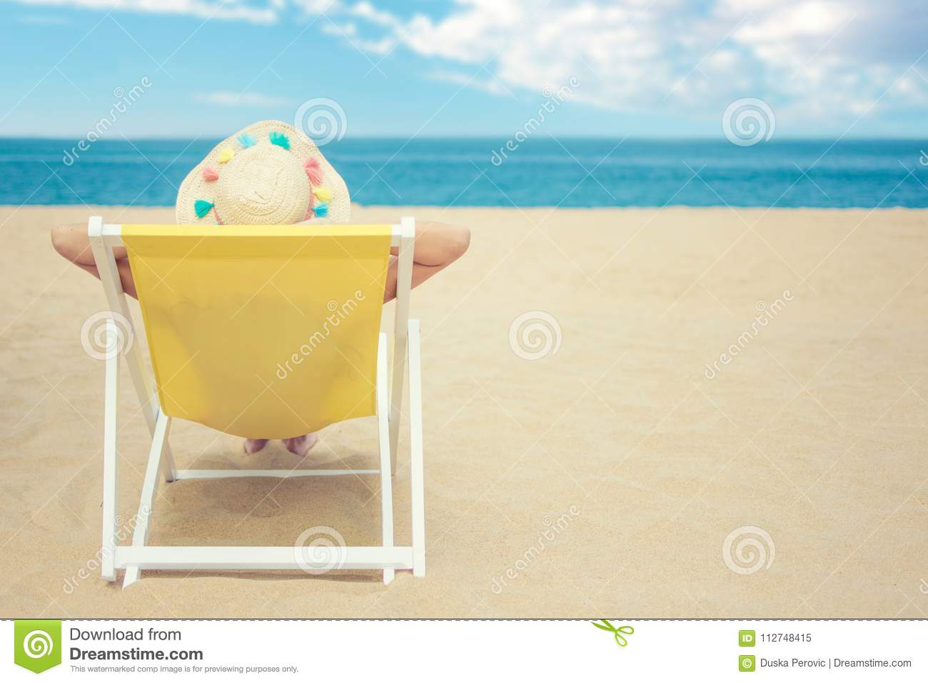 Female tanning on the beach, wearing straw hat, enjoying beautiful seascape, travel and tourism concept