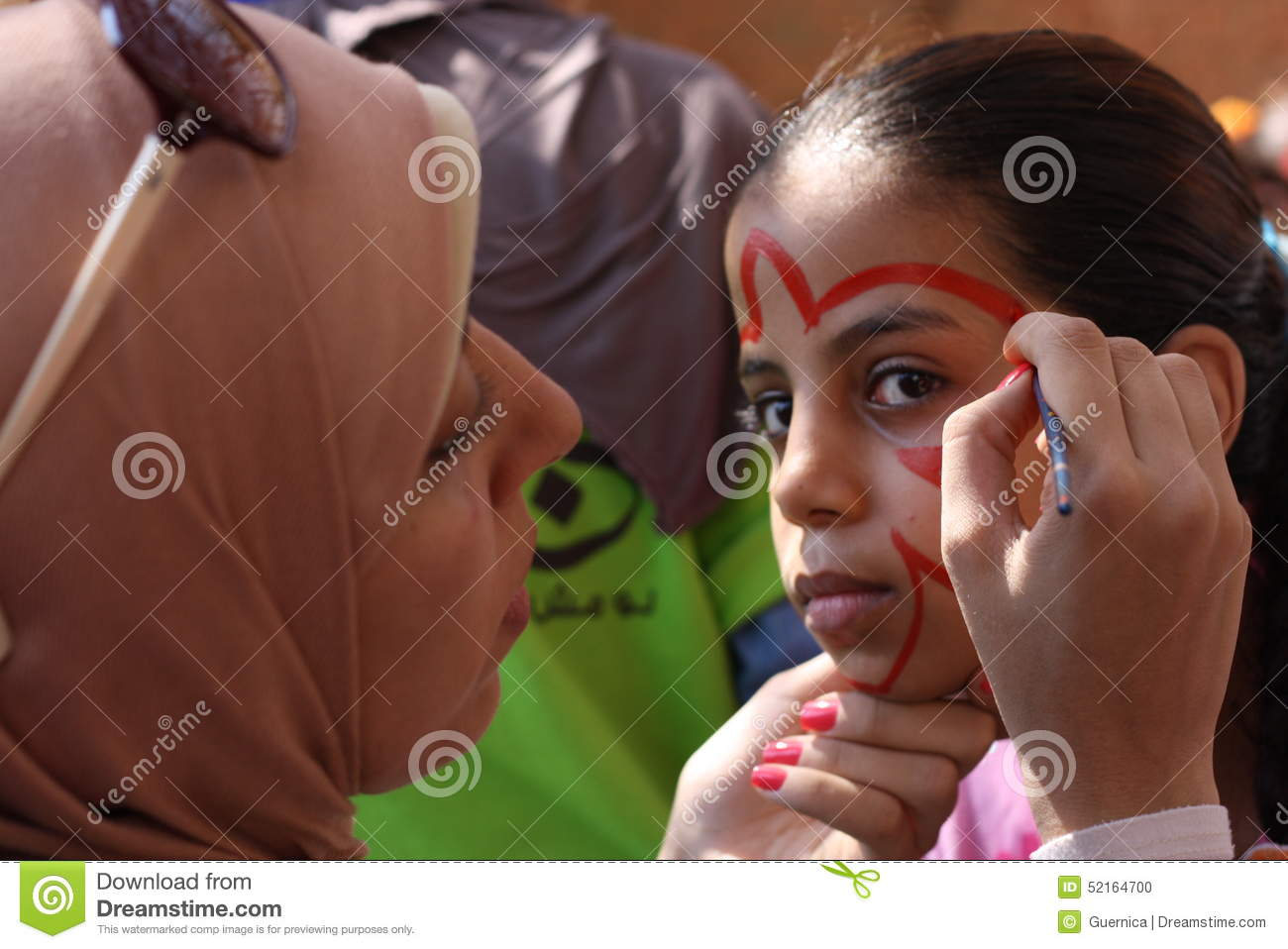 Female teacher painting little girls face in butterfly shape in playground