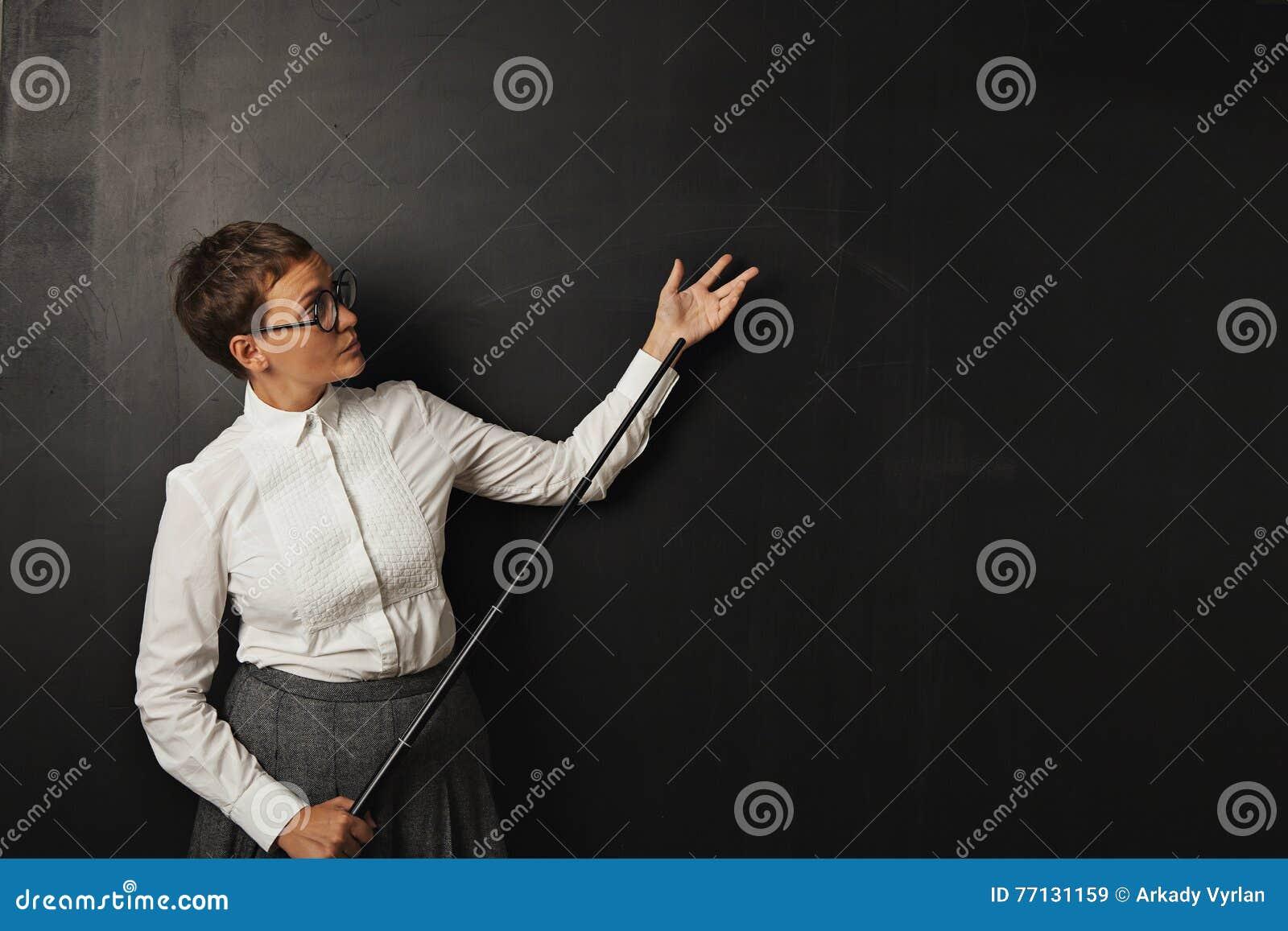 Female teacher with pointer at blackboard