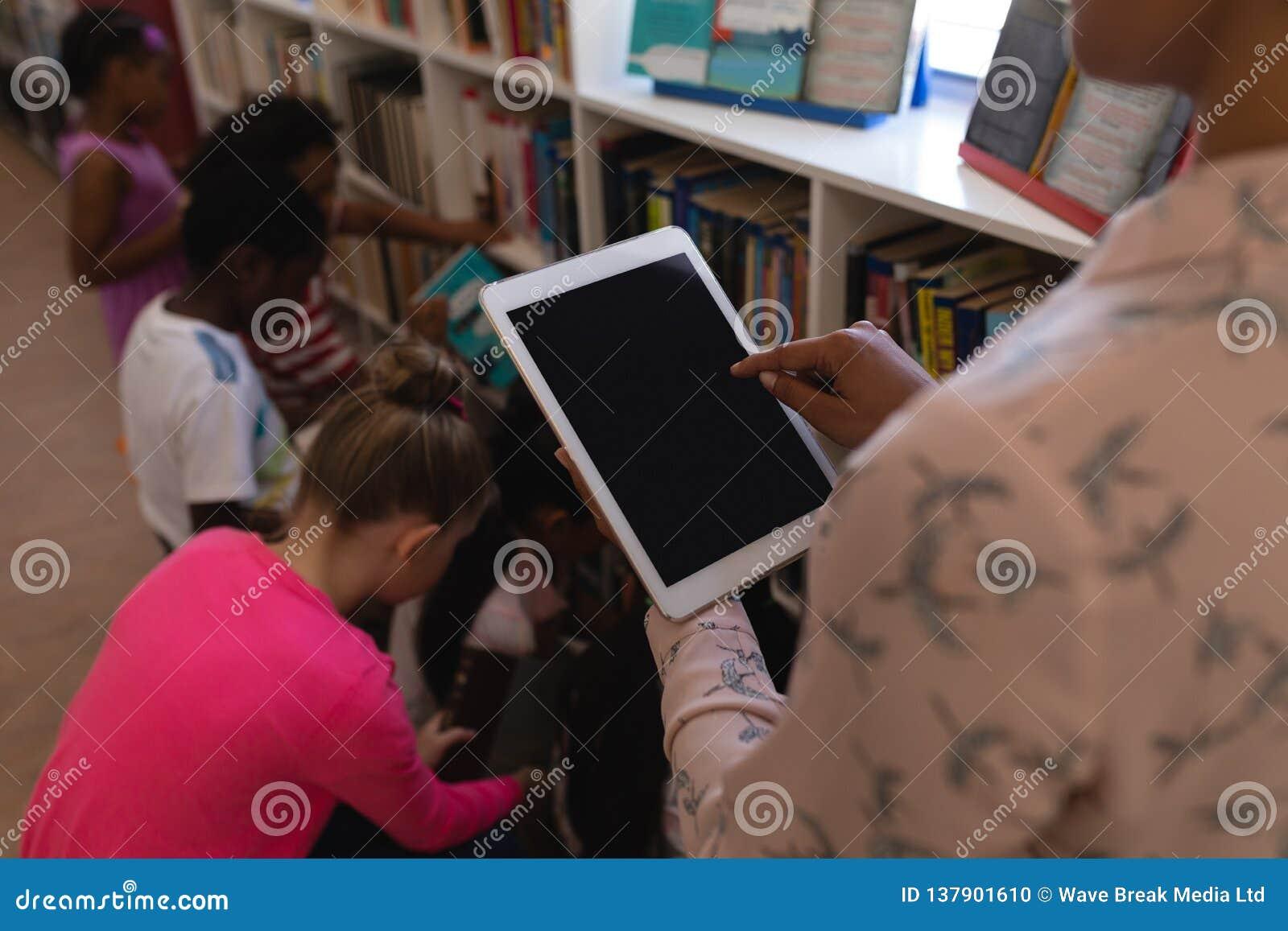 Female teacher working on digital tablet in school library