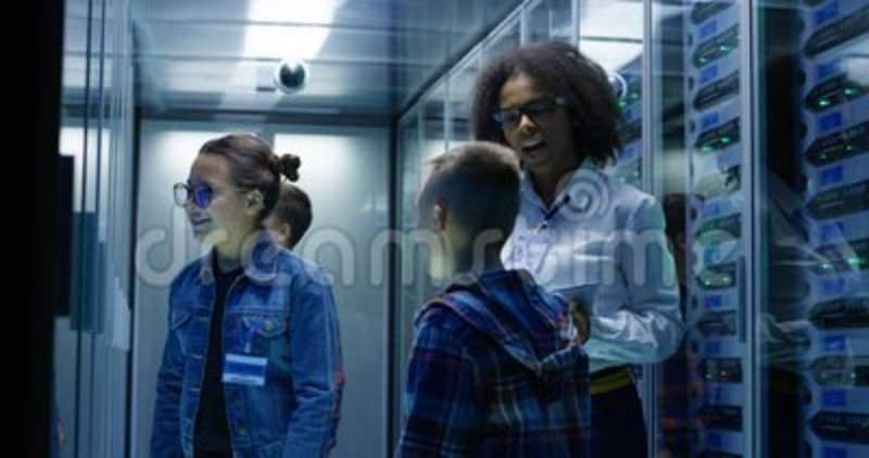 Female technician showing tablet to children. Medium long shot of a young female technician showing tablet to children at a data center stock footage