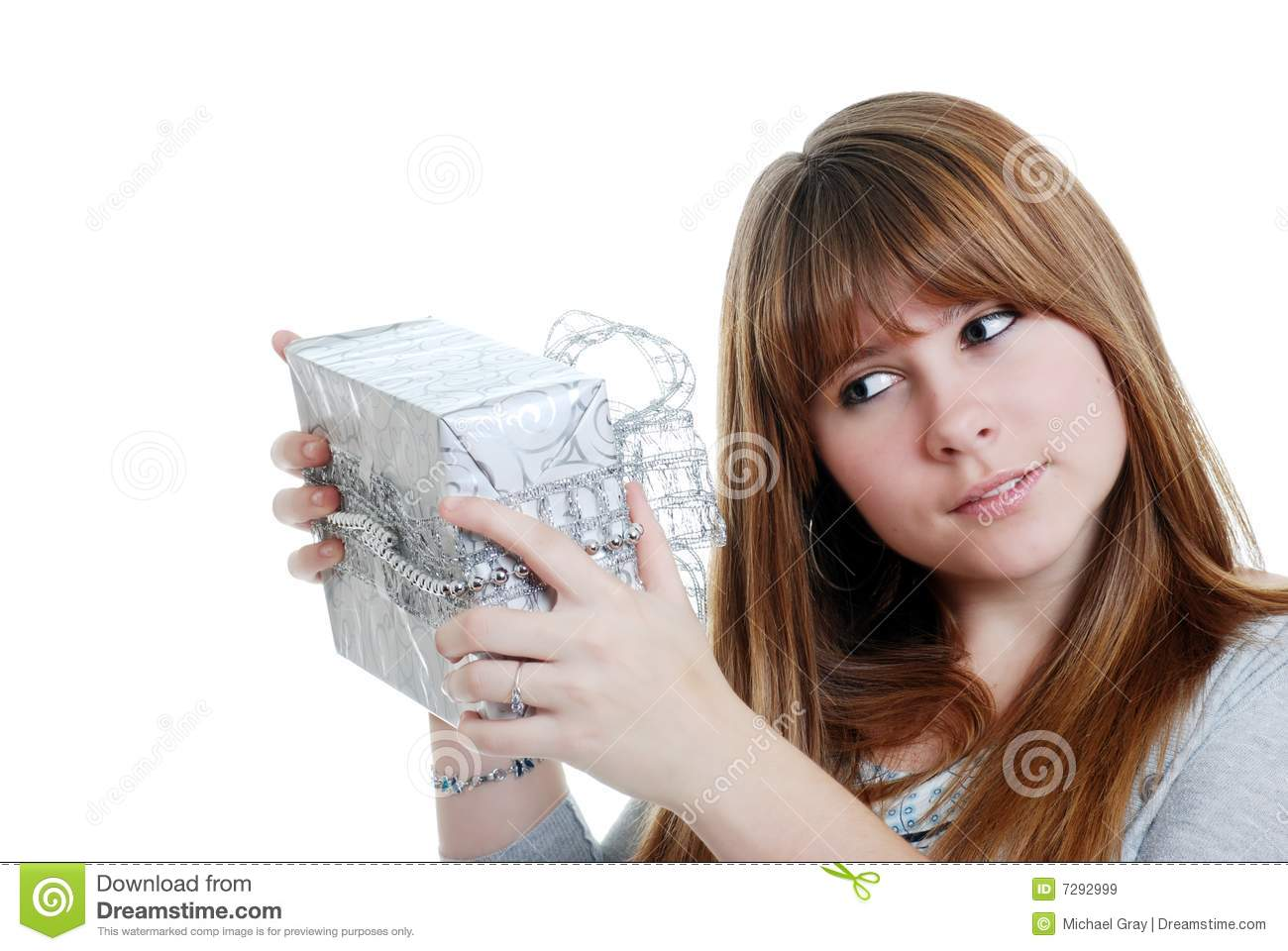 Female teenager shaking a christmas present