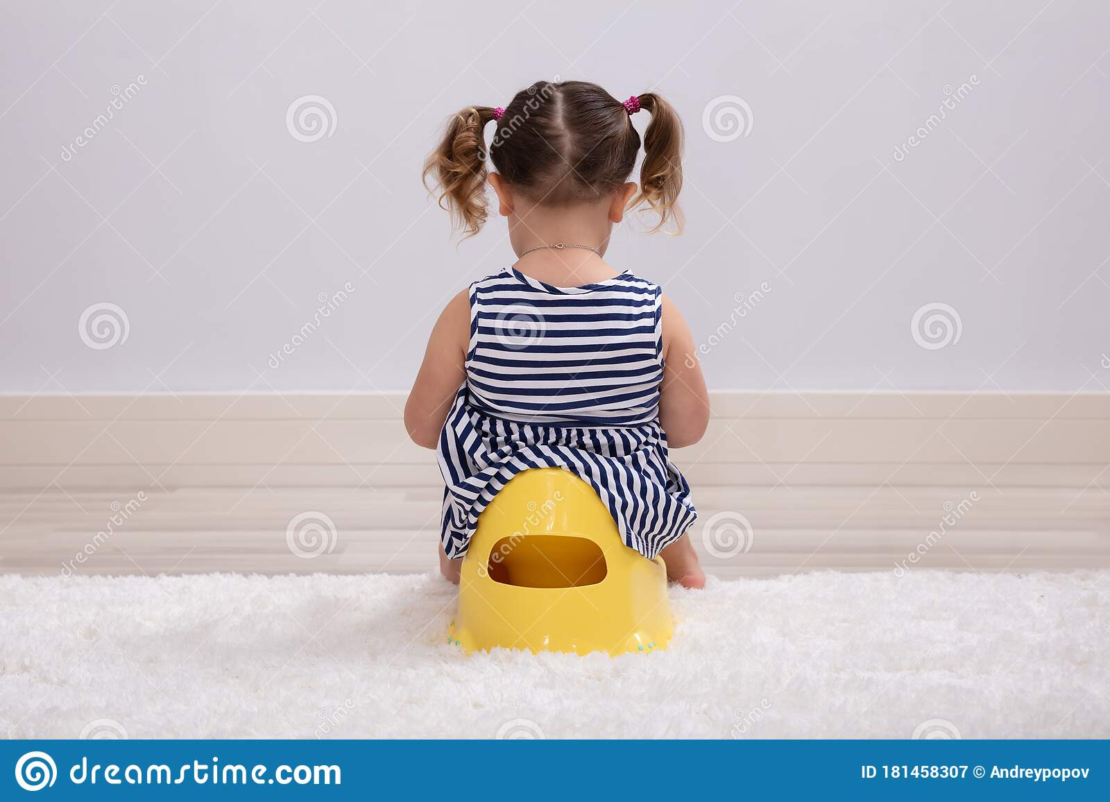 Toddler girl sitting on potty holding toilet paper while