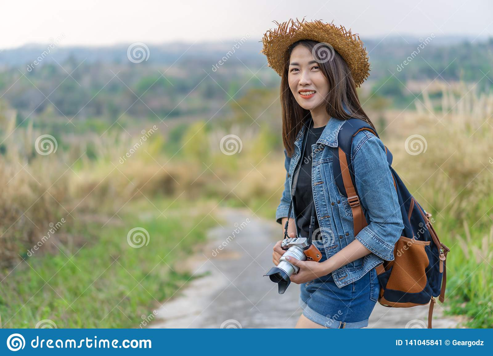 Female tourist with backpack and camera in countryside
