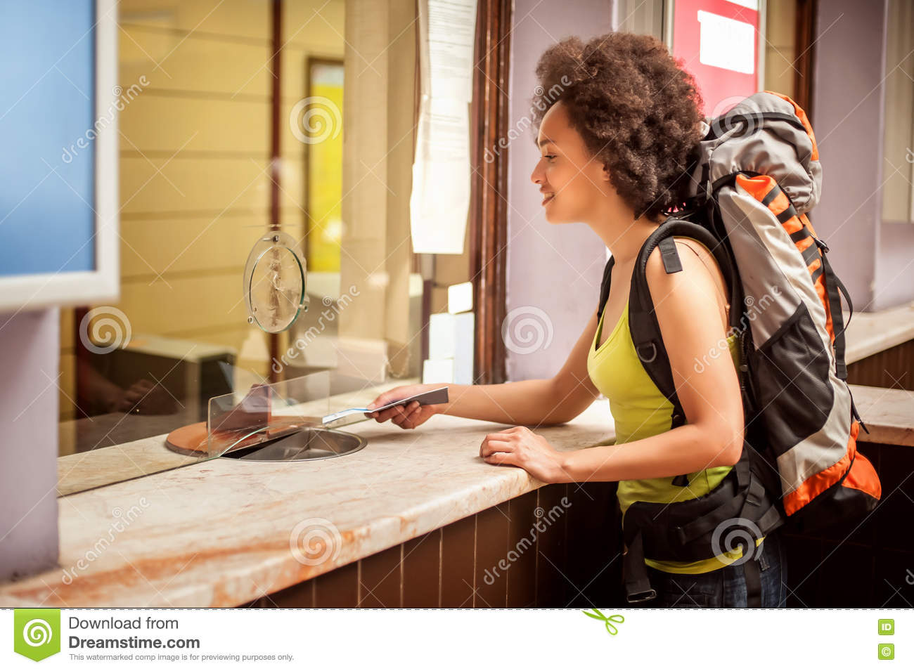 Female tourist buys a ticket at terminal station ticket counter