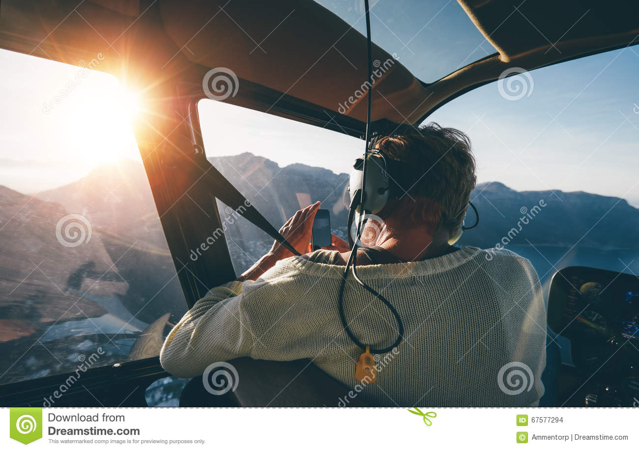 Female tourist on helicopter tour taking pictures
