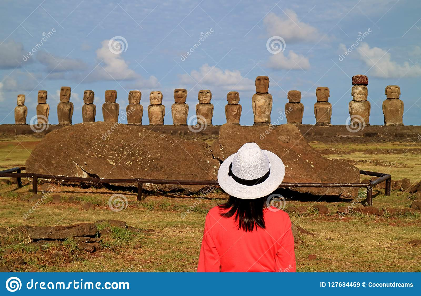 Female tourist impressed by the ruins of Moai statues at Ahu Tongariki on Easter Island archaeological site, Chile