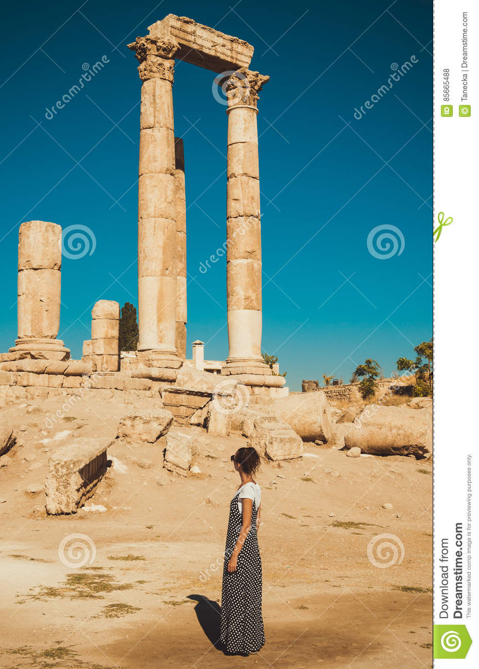 Female tourist in long sundress visit and exploring historic attraction. Woman enjoy summer vacation. Sightseeing tour. Tourism in