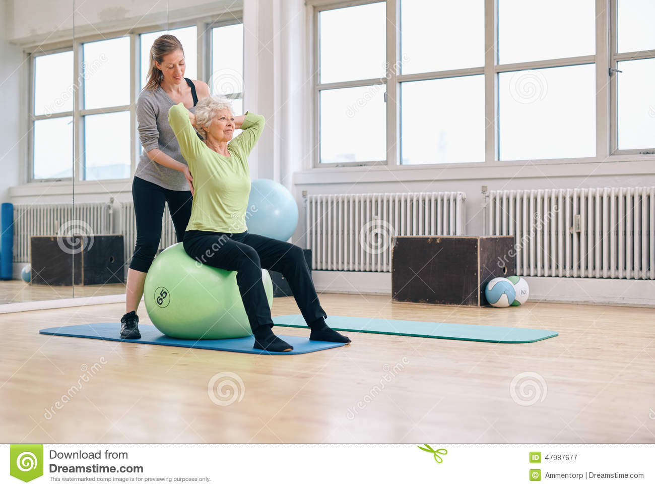 Female trainer helping senior woman exercising in gym for Gimnasio pilates