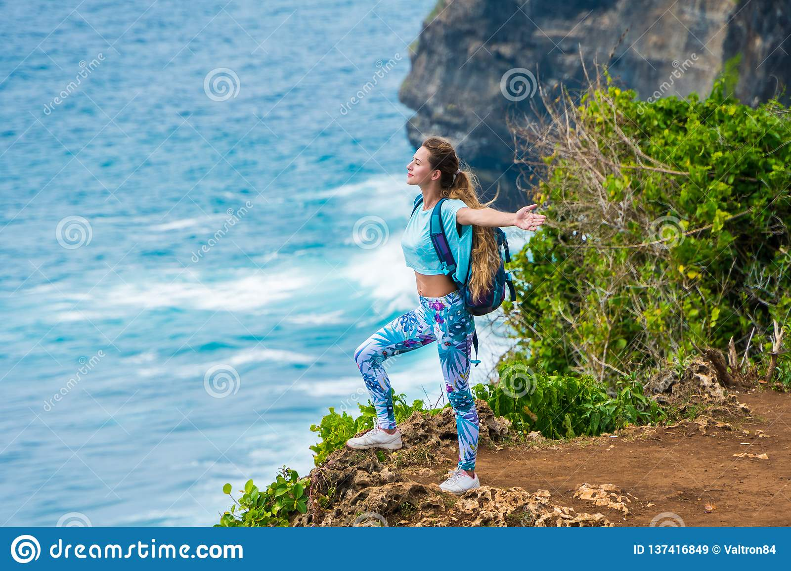 Female traveler with a backpack standing on the edge of a cliff and enjoying the view of the ocean. Bali, Indonesia