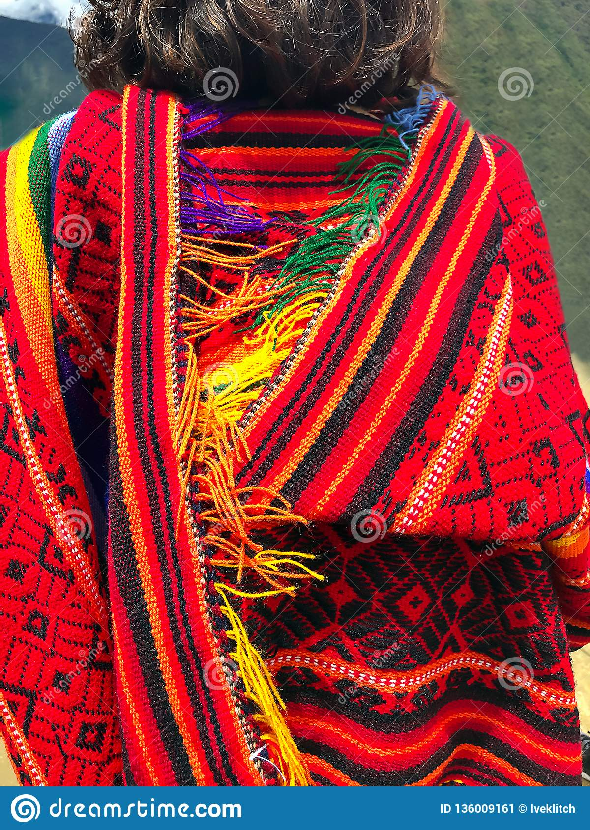 Female traveler dressed in colorful Peruvian poncho in Machu Picchu, one of the New Seven Wonder of The World, Cusco Region,